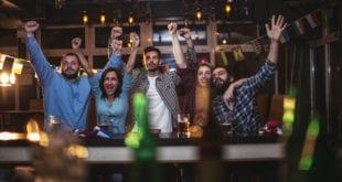 Sports fan celebrating at a bar