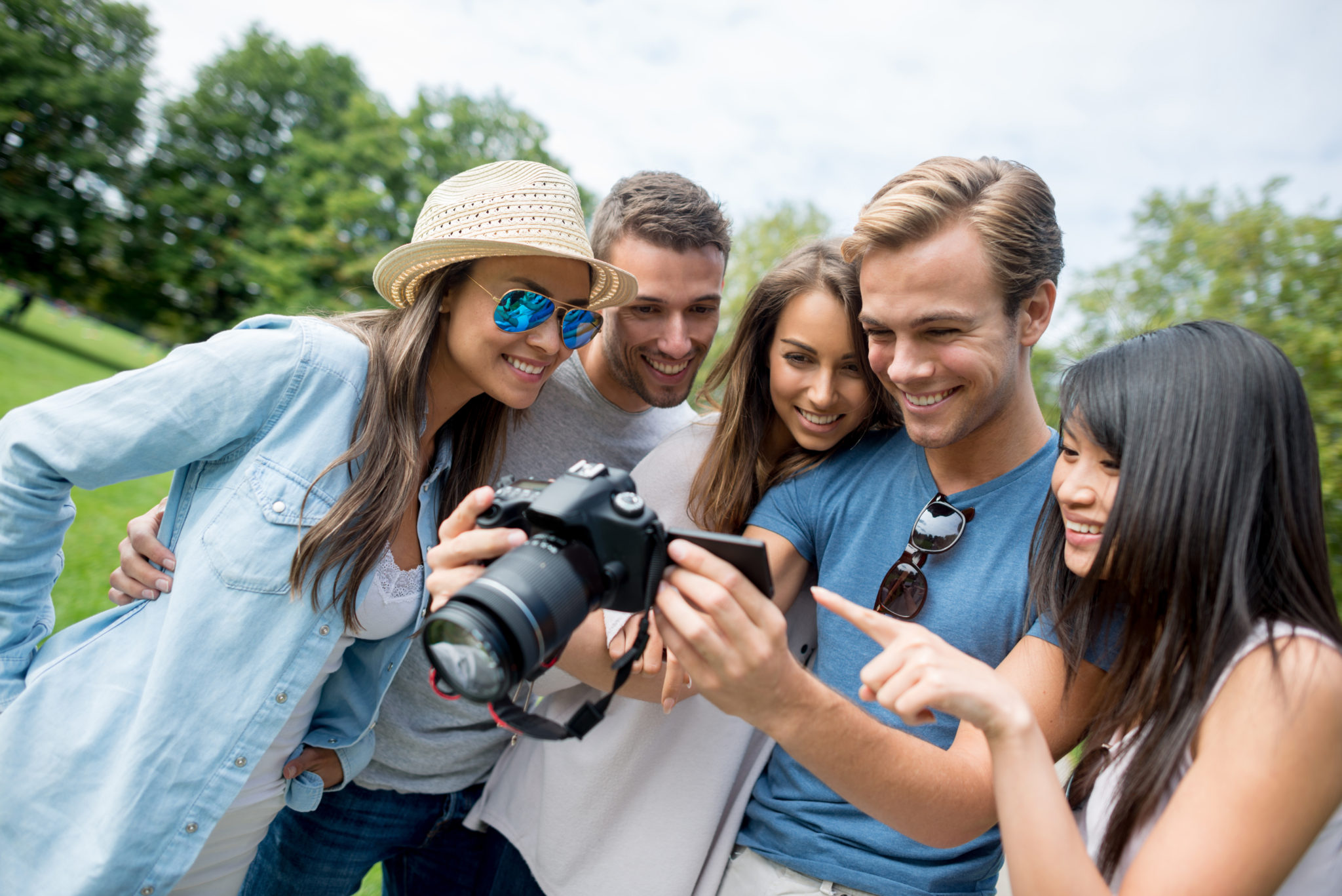 Happy group of friends taking pictures at the park and looking at the display of the camera