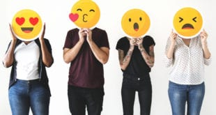 Four people holding emojis