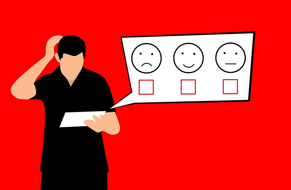 Man looks at rating card showing sad face, happy face and neutral face