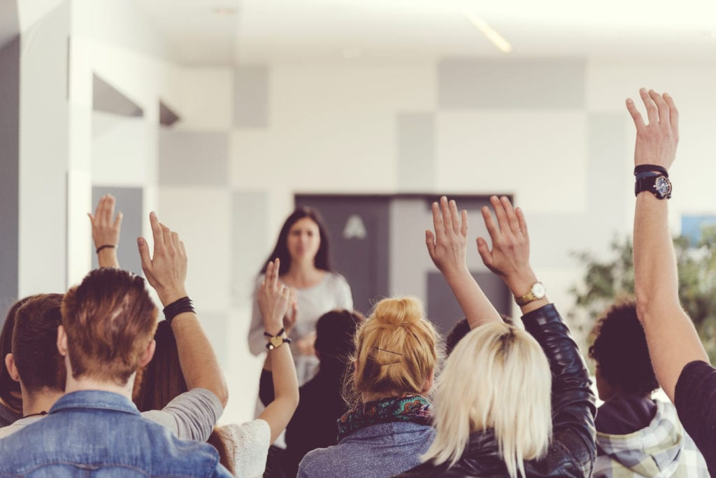 Students raising hands in a classroom seminar